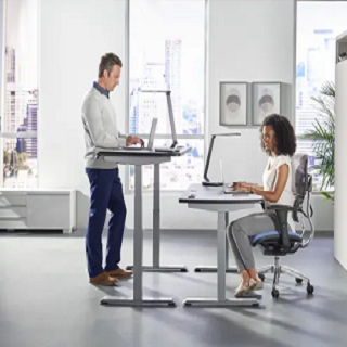 A person working on a sit-stand desk