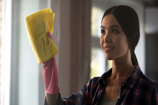 Adult daughter helping mother in general cleaning, washing windows, house chores