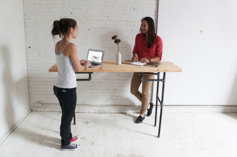 Two employees working on a minimalist standing desk