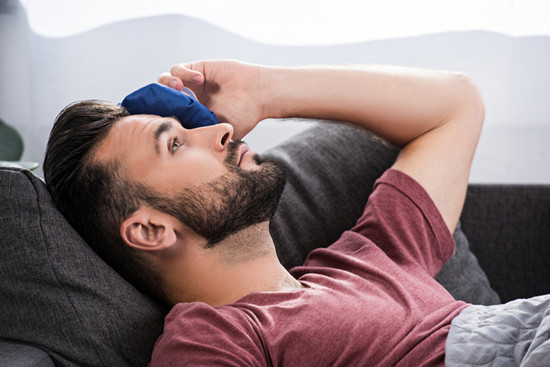 Close up portrait of sick young man lying on couch and holding ice pack on foreh