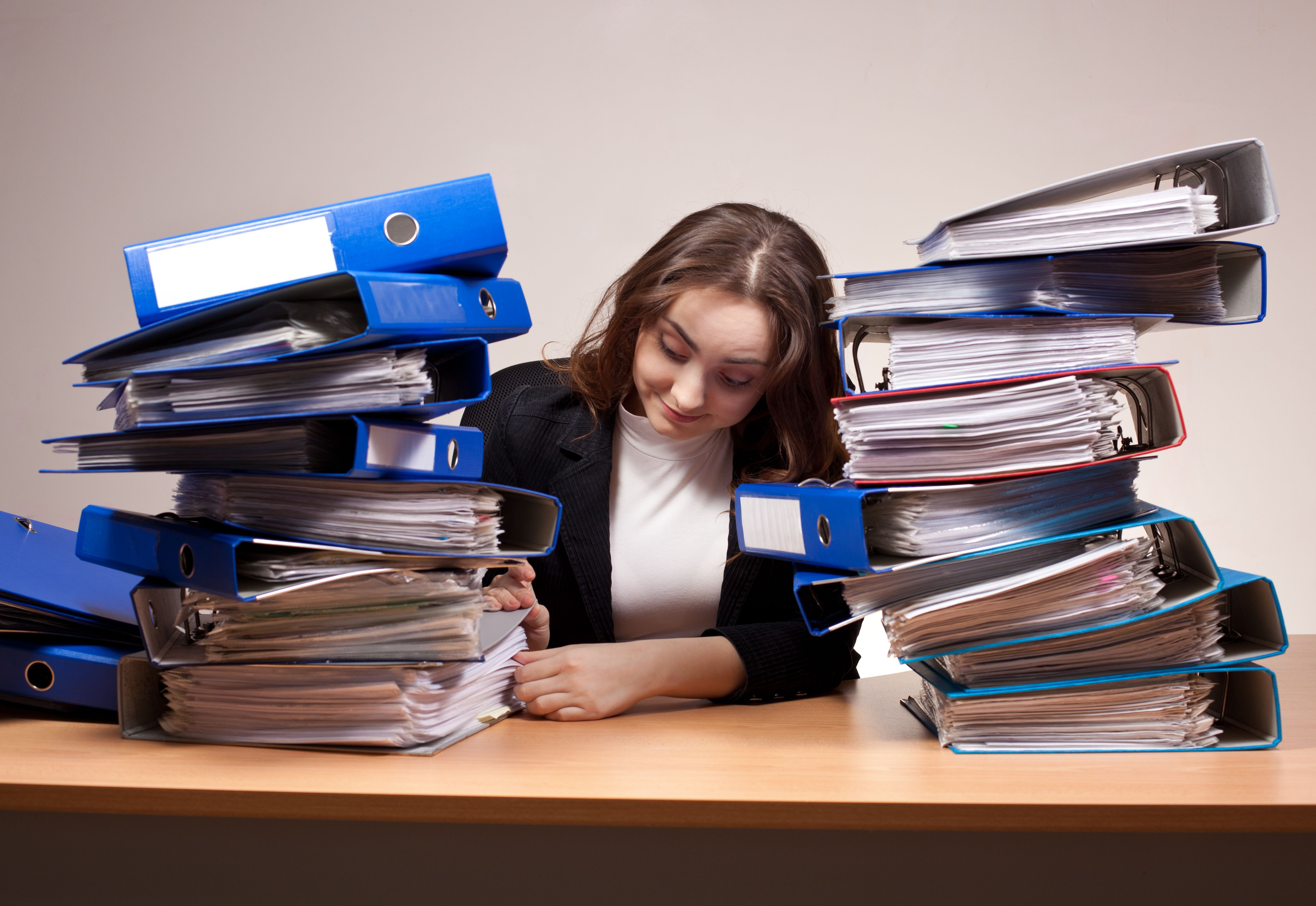 A female staff is surrounded by many files