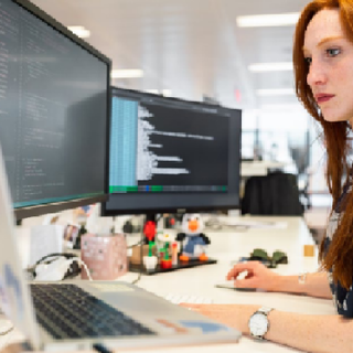 A woman working on multiple screens at the office