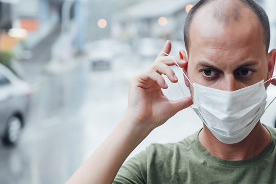 Man putting on a mask with a worried face