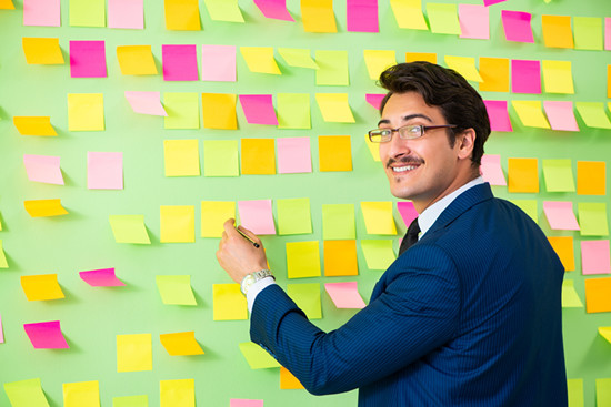 The businessman is standing in front of many notes