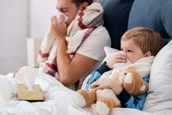 Sick father and son lying on the bed with a tissue to blow his nose