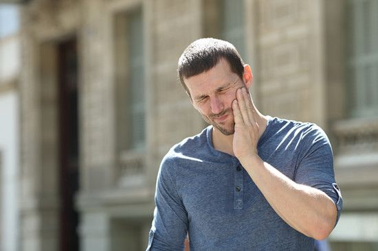 A man is suffering jaw pain which is called TMJ