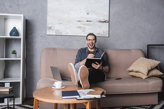 Young happy freelancer working on couch at home office