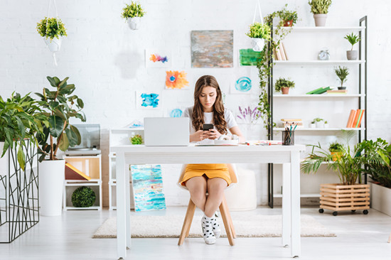 Young woman using smartphone while sitting at desk with laptop in spacious room