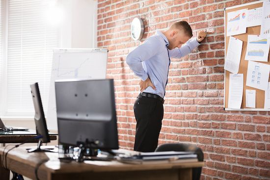 Man stretches up against a wall in his office