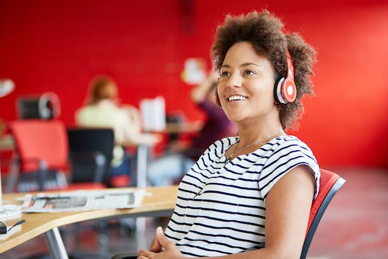 A woman uses headphones to block out noise a work.