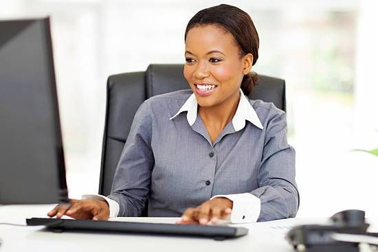 Woman sitting at her work desk looking happy and pain-free.