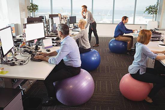 Office workers sitting on exercise balls at work