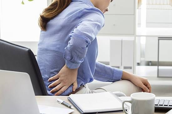 Businesswoman experiencing back pain at work