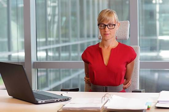 A business woman stretching at her desk.