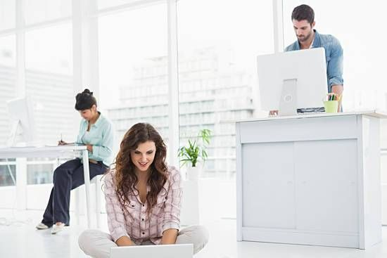 Employees sitting and standing while working at their desk.