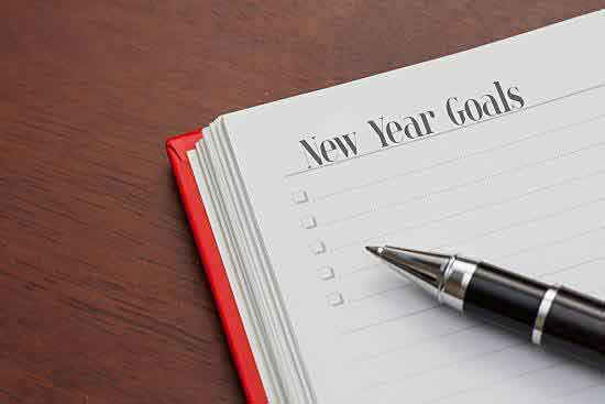 A notebook is open to a list of New Year's goals