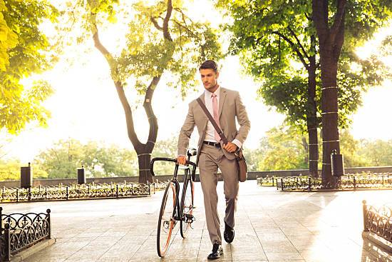 A healthy businessman bikes to work.