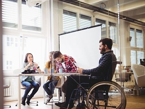A young man in a wheelchair sits at a desk with his peers at work