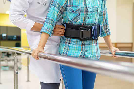 Female patient walking with support from her healthcare provider.