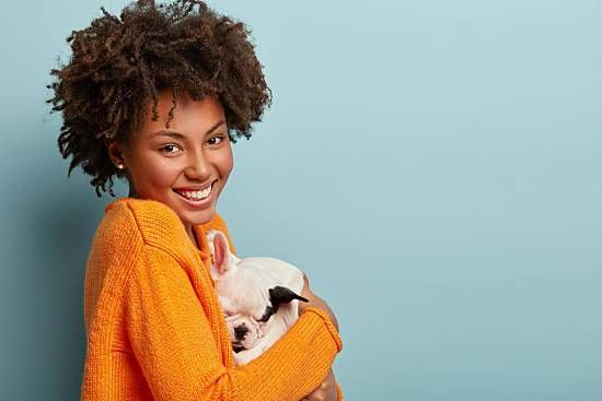 Smiling woman in bright orange sweater holding sleeping puppy