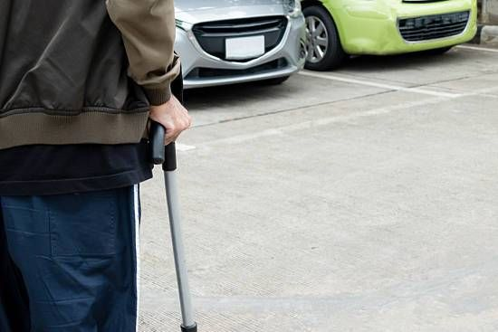 Man walking with cane in parking lot
