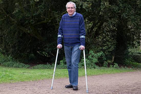 Man on crutches walking outside