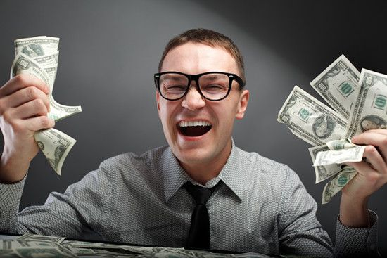 A businessman is laughing with money in his hands