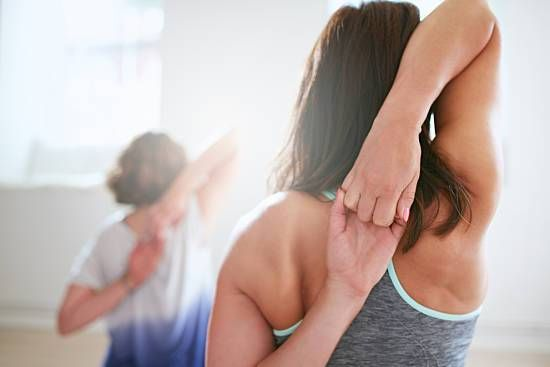 A woman exercises her popping shoulder.