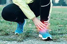 Runner tending to injured ankle joint while in cold weather