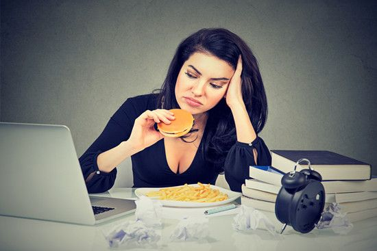 A woman is sitting and eating junk food