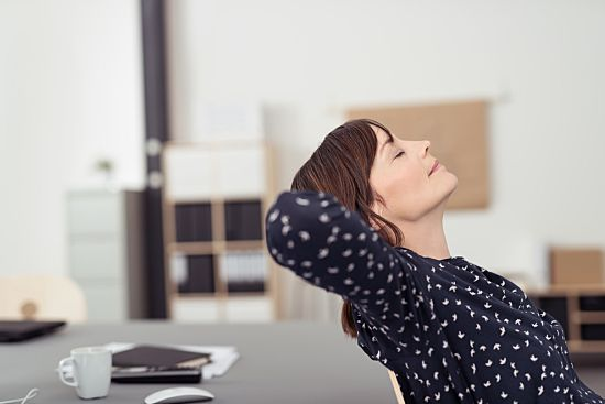 A woman takes a moment to relax and meditate at work to protect her mental healt