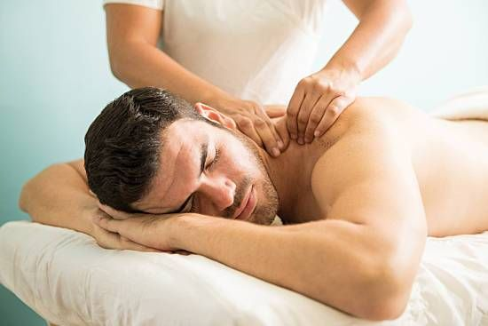 A man receives a deep tissue massage at a spa.