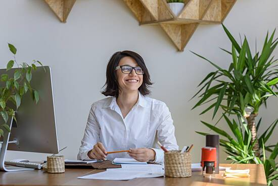 Woman working at a desk, surrounded by plants