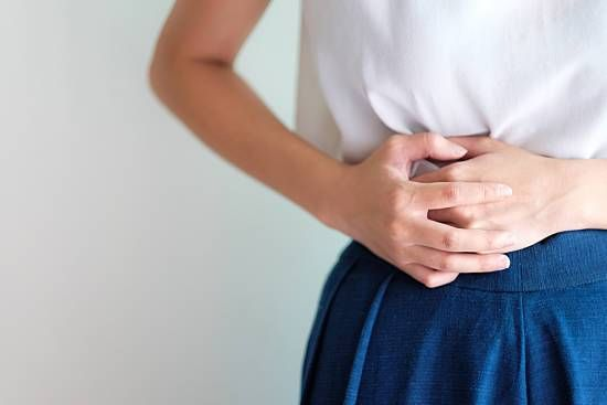 Woman holding belly because of a stomach ache