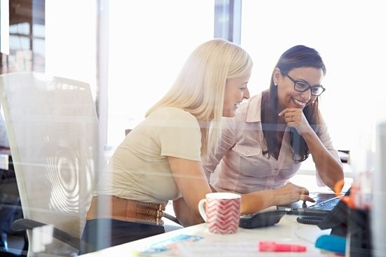 Two women sit together in an office to discuss successful goal setting