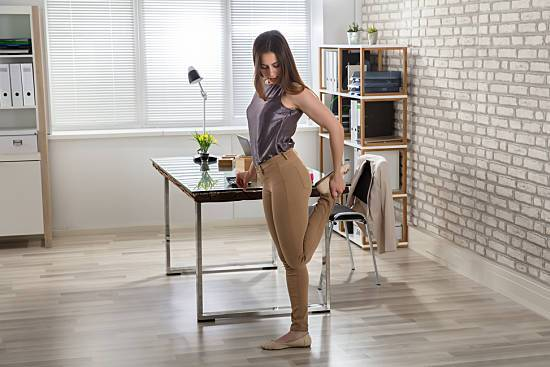 Woman stretching her leg at her desk